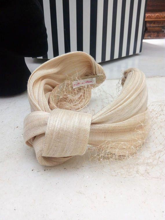Diadema turbante de sinamay y seda en tonos marfil con velo de rejilla incorporado . Este turbante es perfecto para darle un toque originial a tu look de invitada a una boda de día, serás la invitada perfecta. Se puede realizar en otros colores, teñimos nuestras telas en el color