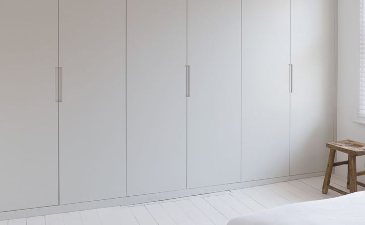 Fitted white bedroom wardrobes with a modern handle detail