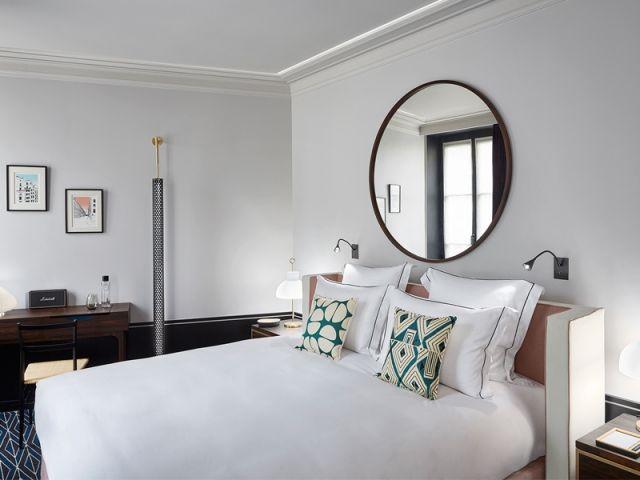 Un miroir rond démesuré en guise de tête de lit