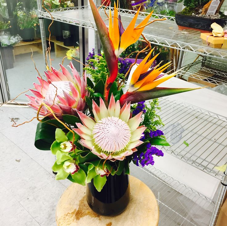Weekly office flowers - featuring Bird of Paradise, King Protea and Cymbidium Orchids by Central Square Florist in Cambridge, Massachusetts