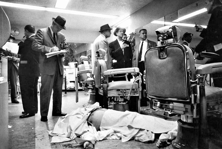 Detectives take notes and examine the barbershop of New York's Park Sheraton Hotel, where the body of Gambino Crime Family Boss-Murder Inc.'s Albert Anastasia lies.