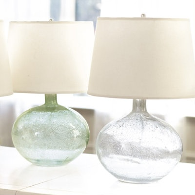 Malia Seeded Glass Lamp: When you turn it on, the seeded glass gourd base becomes an instant focal point. Hand crafted with hundreds of subtle bubbles and striations that gives seed glass its unique quality. We chose a tapered drum, off-white linen shade included to complement the versatile shape. $119 http://www.ballarddesigns.com/malia-seeded-glass-lamp/lighting/table-lamps/203930