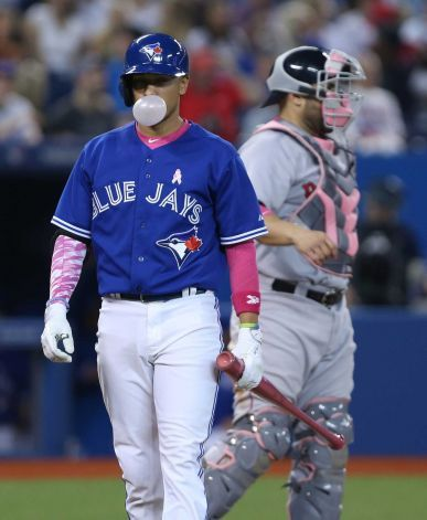 Toronto Blue Jays second baseman Ryan Goins (17) blows a bubble of pink gum during an at bat in the 7th inning of AL baseball action between Toronto and Boston in Toronto on Sunday, May 10, 2015. Many players wore or used pink items of equipment during the Mother's Day game. (Peter Power/The Canadian Press via AP) MANDATORY CREDIT Photo: Peter Power, AP / CP