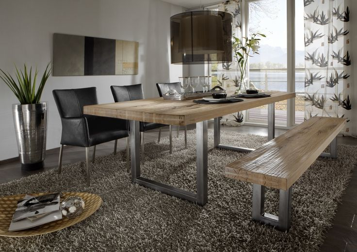 Der Esstisch aus massiver Balkeneiche mit aufgedoppelter Plattenstärke ist ein Möbelstück der Extraklasse und verleiht dem Raum ein exklusives Wohnambiente. Das warme und beruhigende Naturschauspiel des Holztisches  wird verbunden mit zeitlosem Designanspruch. Designerleuchte, extravagante Hochlehner mit Leder bezogen und die unauffällig gemusterte Gardine weisen auf Geschmack und Stilbewusstsein hin. Der beigegraue Hochflorteppich bringt wohnliche Gemütlichkeit in den Raum.