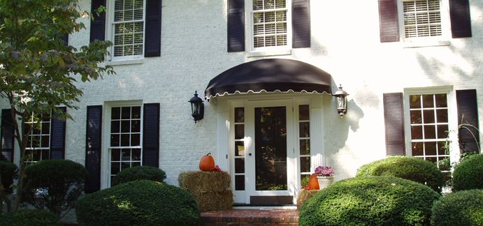 White House With Black Canvas Awning Outdoors