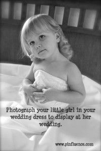 Photograph your little girl in your wedding dress to display at her wedding.