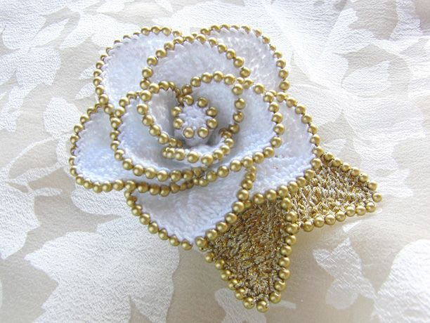 【作品の特徴】 小粒のパールビーズをふちに編みつけたかぎ針編みのバラに、コサージュピンとヘアクリップの2way金具をつけました。 花びらにふち...