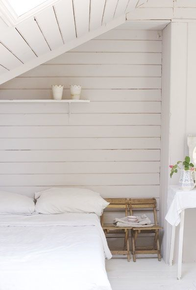 I love the slanted ceiling with the skylight. The room is so beautiful with the natural wooden planks painted white.