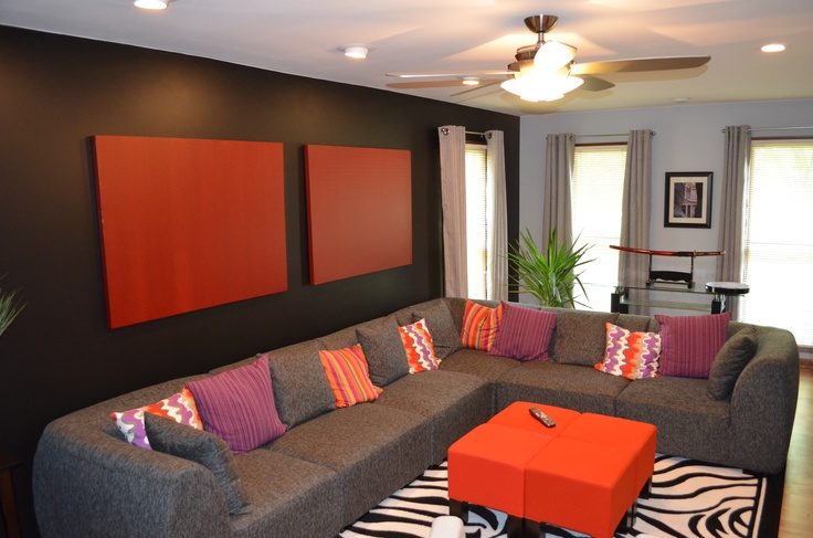 Living room black wall red canvas orange ottomans for Grey orange living room
