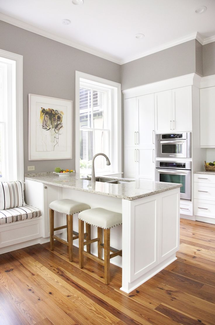 White cabinets and trim, gray walls, marble look tile, wood floors and blinds, stainless accents, black furniture.