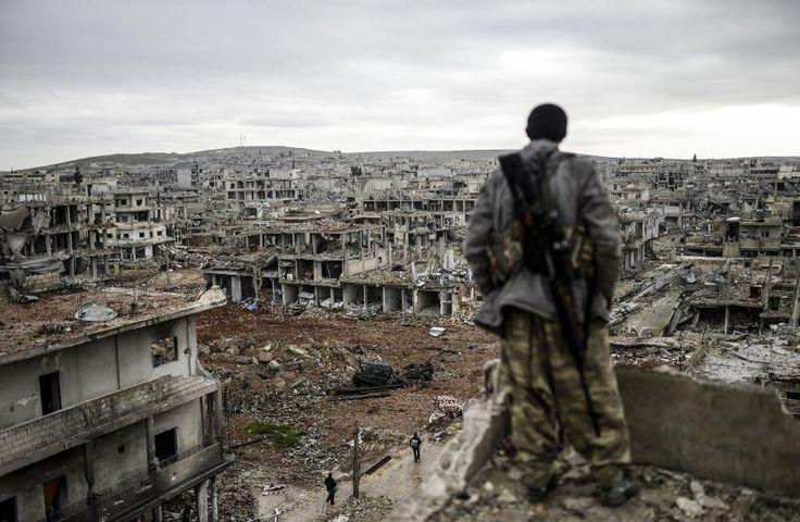 Musa, un tirador kurdo de 25 años de edad, se encuentra en lo alto de un edificio mientras mira a la ciudad siria destruida de Kobane, también conocida como Ain al-Arab. 30 de enero de 2015. Las fuerzas kurdas recapturaron la ciudad en la frontera turca el 26 de enero en un golpe simbólico a los yihadistas que se han apoderado de grandes extensiones de territorio en su ataque a través de Siria e Irak. Bulent Kilic—AFP/Getty Images.
