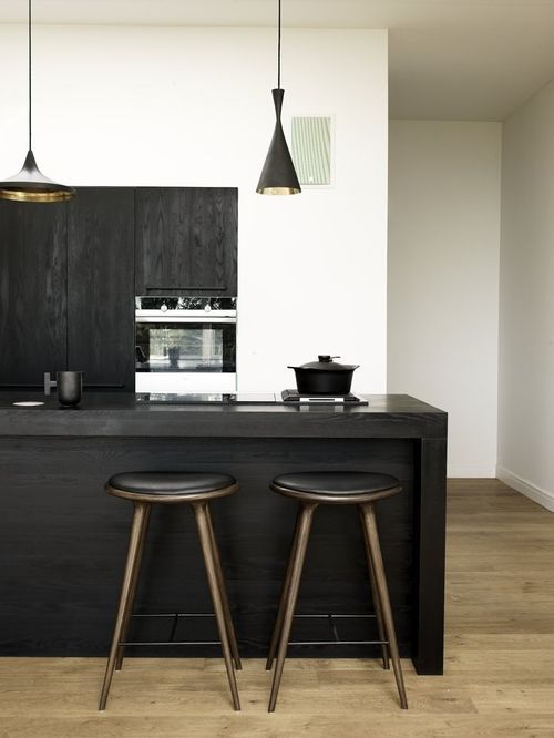 Bar stools, dark, minimal kitchen with white walls and wood flooring