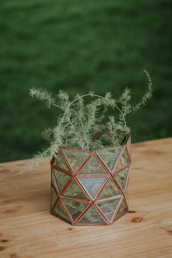 Copper geometric wedding centerpiece with greenery | Image by Page & Holmes Photography