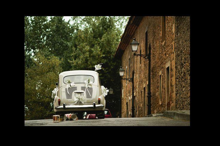 Vehículos nupciales para novias y novios el día de su boda: un 600 decorado con ramilletes y arrastrando latas