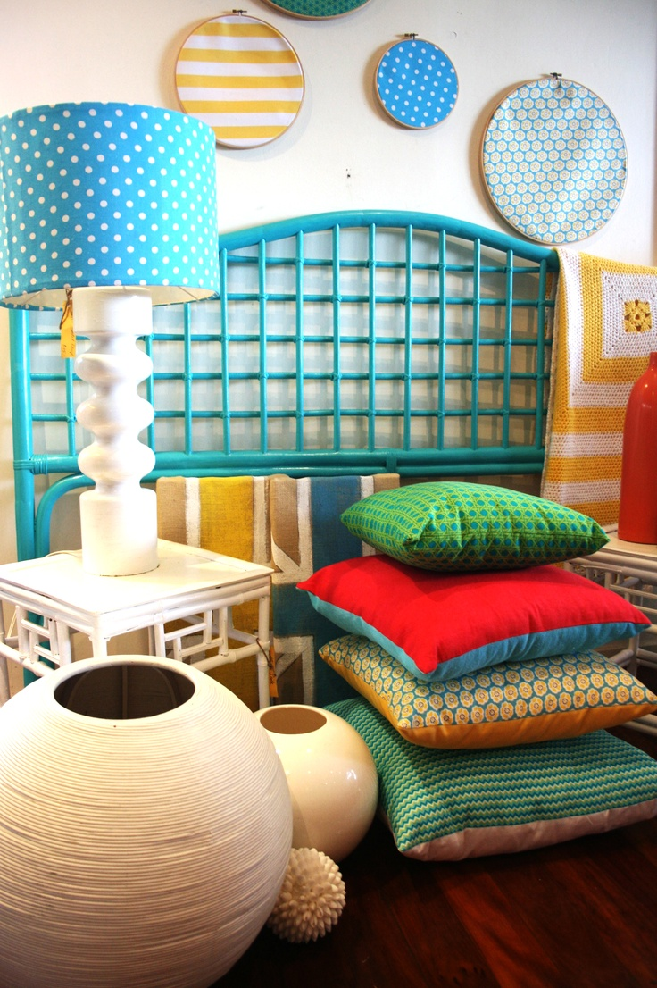 Tiffany and Co blue cane bedhead, retro cane sidetables, yellow white striped nanna blanket, retro lamp with turquoise polka dot shade, selection of turquoise,yellow, grass green retro print cushions, embroidery hoop fabric art, spherical vases, and blue and yellow burlap union jack art.