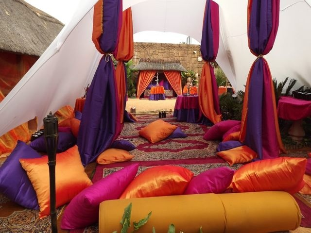 Arabian themed event with arabian themed decor, white stretch tent, arabian carpets, draping, pillows, low level seating