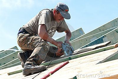 Roofer at work on top of a house using an electric saw.