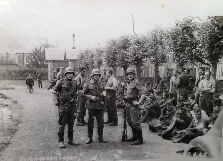 (8/12) German soldiers stand guard in front of dozens of Allied prisoners after the Dieppe Raid, 19 August 1942.