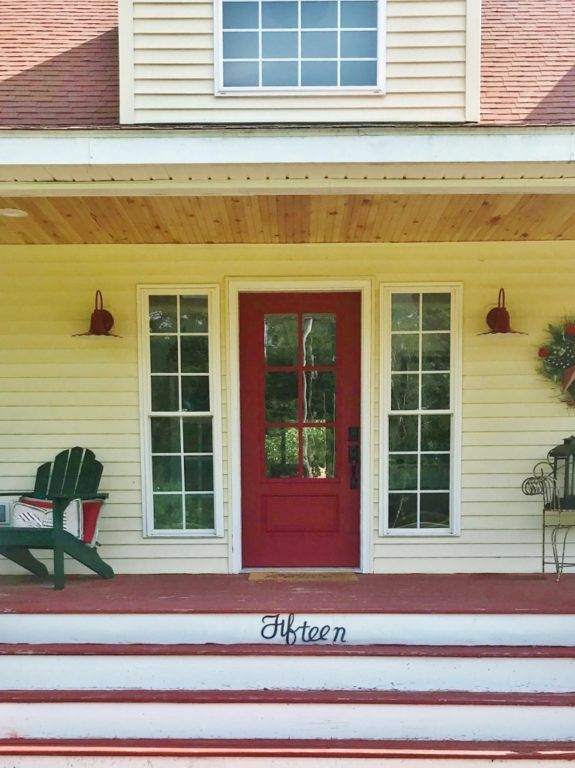 With Its Bright Red Door And Playful Wall Lights This Front Porch Features A Timeless Farmhouse Style Farmhouselighting Frontporchlighting
