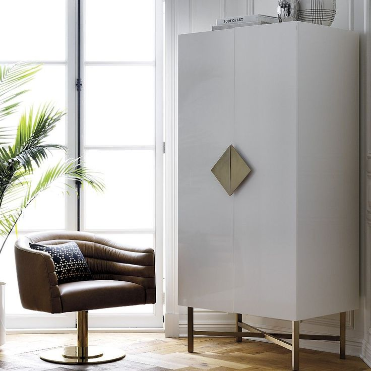 Shop astoria white wooden wardrobe. White wardrobe gleams as haute hideout for clothes and clutter. Designed by Ceci Thompson, steel legs and solid frame support one fixed shelf and removable brass pole for hanging clothes.