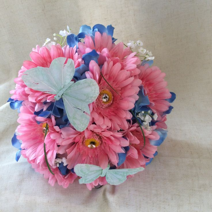 Pink gerbers, blue hydrangea with gyp finished with butterflies by Cathey's flowers
