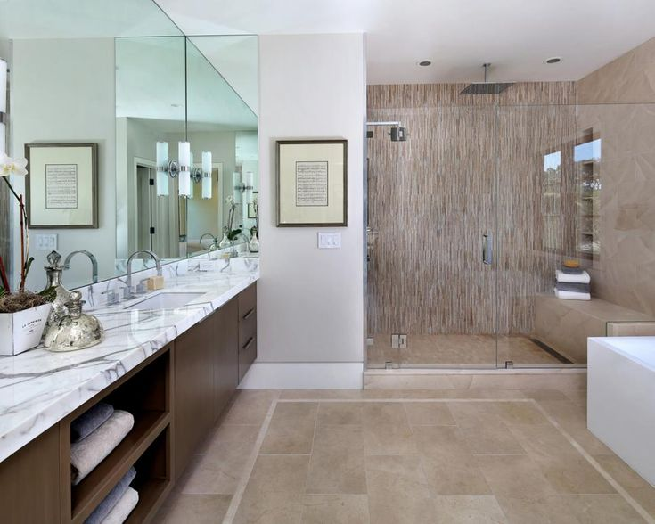 this sleek neutral bathroom features a brown contemporary double vanity with marble countertops and a wall