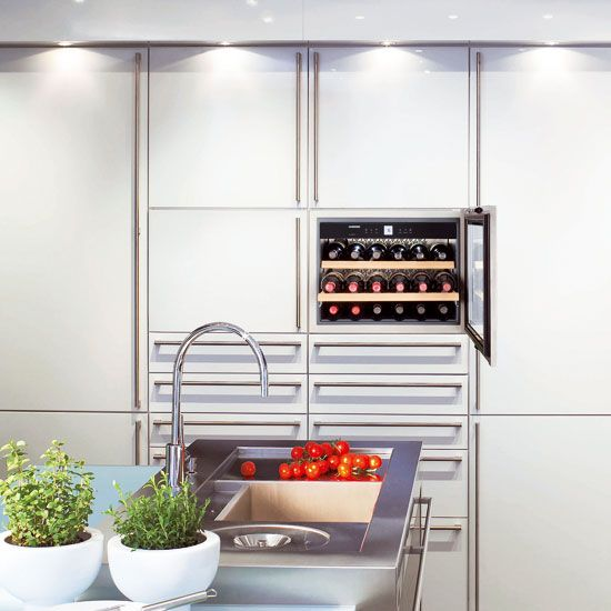 Small kitchen with white cabinetry, wine cooler, stainless steel sink and living herbs