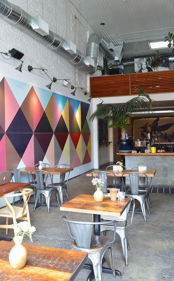 parede tijolos brancos, teto telha ondulada, quadro colorido, cadeiras tolix, dutos aparentes, madeira