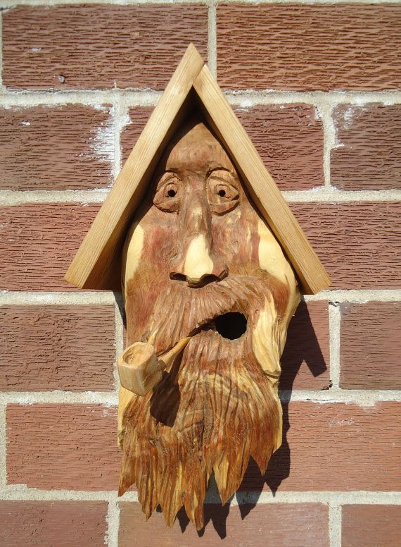 Very unique cedar wood birdhouse, complete with a hand carved face made out of a thick piece of cedar wood.