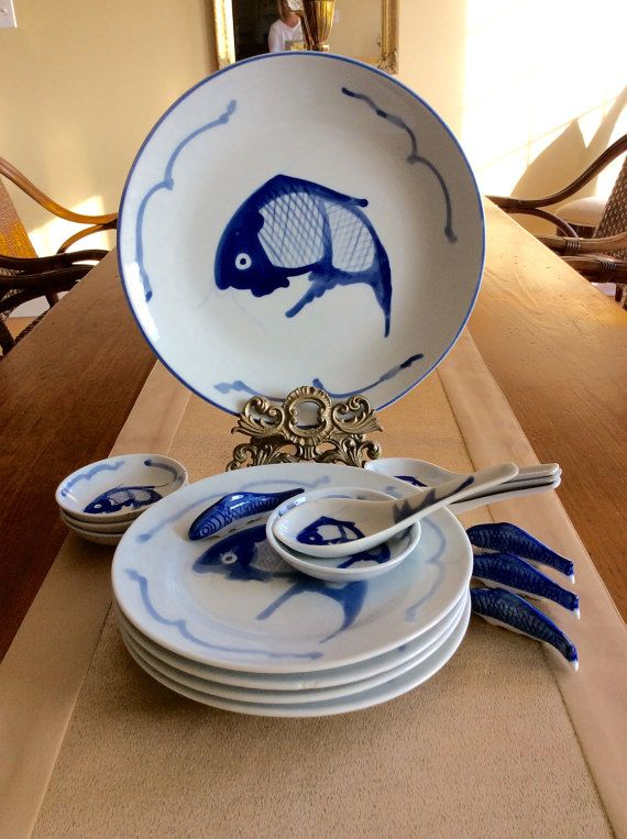 What a beautiful set of four sushi diningware dishes. Set includes 4 plates , 4 dipping bowls, 4 spoons, 4 fish chopstick rests & one large platter plate. All are decorated with a koi fish & wave design in blue & white. Decorative chopstick rests are porcelain koi fish. In very good vintage condition, there are slight imperfections in the molding process to porcelain, but no chips to any of the items. Great for anyone who loves sushi & Asian dining!  Shipped insured!  Measures platter…