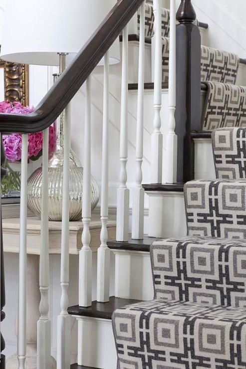 Chic foyer features white staircase accented with dark stained stair treads and white spindles lined with a gray and black chain link stair runner.