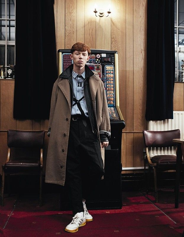 King Krule wears overcoat by Ermenegildo Zegna; leather jacket from the Vintage Showroom; printed shirt by Yohji Yamamoto; tuxedo trousers by Haider Ackermann