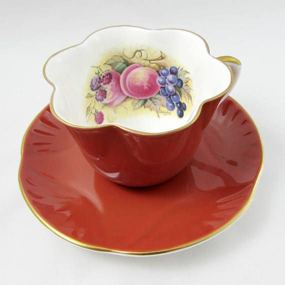 Bone china tea cup and saucer made by Crown Staffordshire. Tea cup and saucer are orange. Tea cup has fruit on the inside rim, signed by the artist (J Bailey). Gold trimming on cup and saucer edges. Excellent condition (see photos). Crown Staffordshire produced tea cups from 1897 until