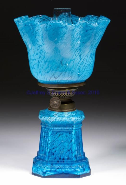 """with opal flakes, slightly tapered columnar-form font with flat and ribbed corners, each window with a frosted embossed floral petal, matching spatter shade with scalloped top, period collar. Fitted with a period burner, colorless chimney. Fourth quarter 19th/early 20th century. 9"""" H to top of shade, 4 1/8"""" H to top of collar, 3 3/8"""" SQ base. <BR><I>Undamaged lamp and setup, shade with a small spot of undissolved metal, as made.</I><BR>Literature: Parallels Hulsebus - Miniature Lamps of…"""