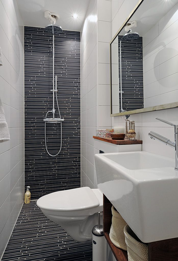 Inspiration from Bathrooms.com: Another lesson in how to trick the eye into seeing a narrow space as wider: here, pencil thin tiles are fixed horizontally both on the back wall and floor, plus they're reflected in the mirror. Clever. #whitebathrooms #bathrooms #showerrooms #wetrooms