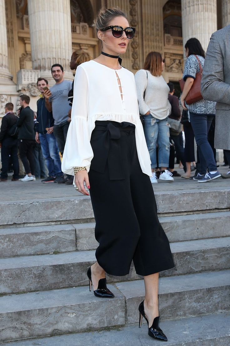 Olivia in a flowing peplum L'Academie chiffon blouse tucked into black Tibi culottes, Gianvito Rossi heels, an Alexandre Birman leather choker and cat-eye frames.