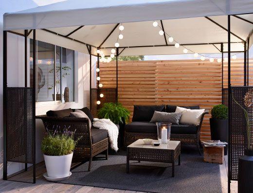 Uteplass med to sofaer og et bord i brunsvart plastrotting med svarte sitte-/ryggputer. Alt samlet under et hagetelt med lyslenker til utendørs bruk.