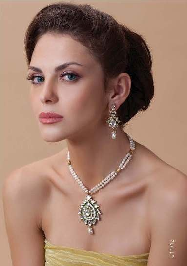 Necklace and earrings in gold finish with kundan stones and pearl beads priced at $179.