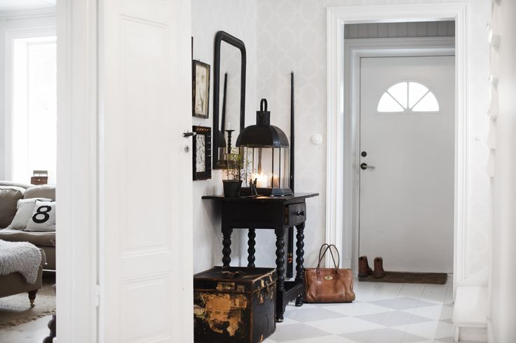 Spacious and light entryway. Combination of white and darker natural colours.