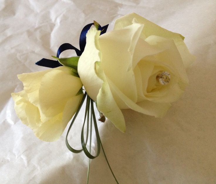 Ladies Buttonhole in Ivory Avalanche Rose, Lisianthus finished with loops of Navy ribbon