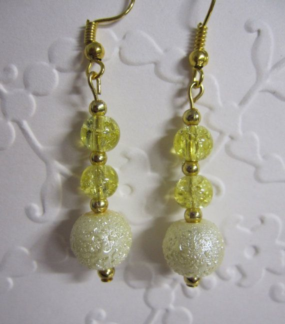 Pearl finish drop earrings with yellow/green crystal beads with gold fittings.