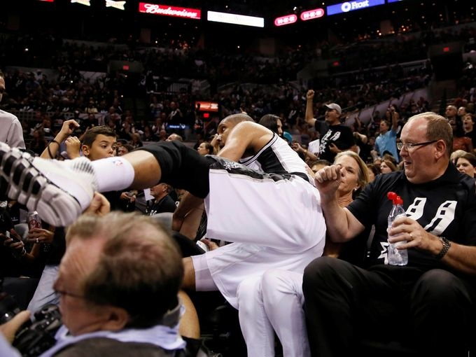 NBA Finals - Game 3 - Tim Duncan of the Spurs dives for a loose ball and ends up on the fans