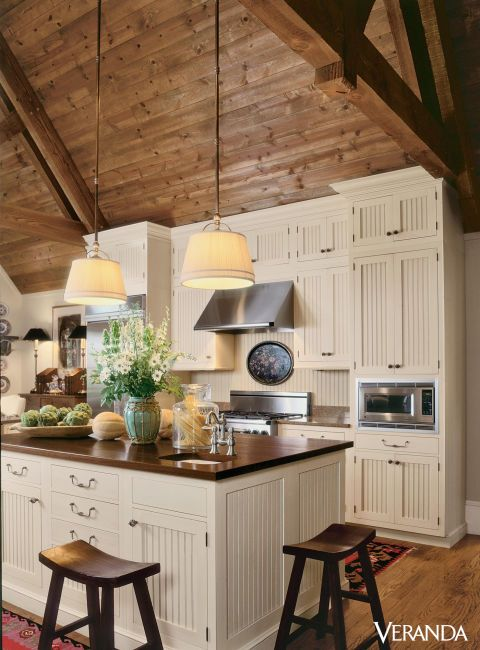 This rustic kitchen features a sloped wooden ceiling leading to beadboard cabinets and island with chopping-block top, all by Wood-Mode.