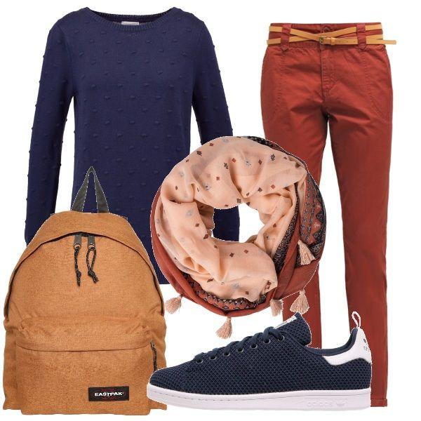 Pantaloni color mattone e pullover blu navy con piccoli pois in rilievo, sneakers basse blu, foulard nei toni del mattone e del cipria e zaino color caramello: ecco il look perfetto per la lezione all'università.
