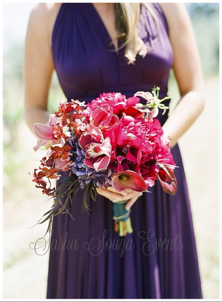 Daily Pretty:  Color saturated bridesmaid bouquet with hot pink peony, cymbidium and oncidium orchids, hydrangea, gloriosa lily and dark toned foliage. Stems encircled in peacock satin ribbon with gold chain accent.  Image by Tanja Lippert