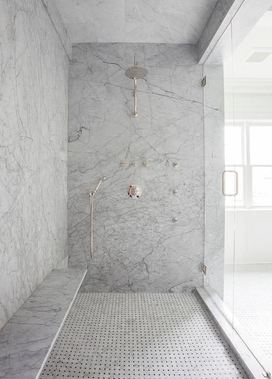 Exquisite shower is fitted with gray marble slabs lined with a marble floating shower bench over a marble basket weave shower floor.