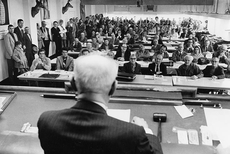 1973 - A view from the stand of the American Legend (formerly Seattle Fur Exchange) auction room.  It is filled with buyers at tables ready to bid on mink pelts and mink ranchers lining the room to watch their pelts being auctioned off.