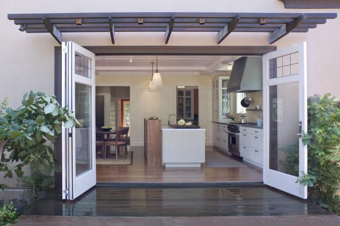 The opening to the rear garden is 18 feet wide, and Buttrick installed a full-height, wooden folding door to maximize the sense of indoor/outdoor flow. Single pane leaded glass at the top of the doors recalls the Craftsman details in the hall and stair.