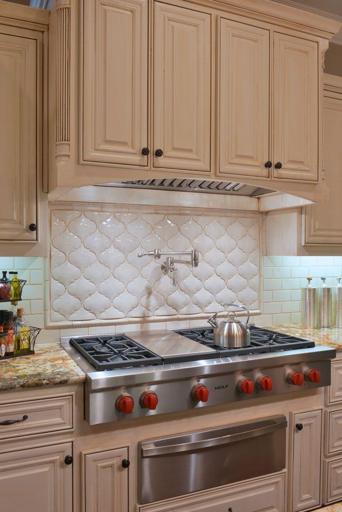 Kitchen with unusual backsplash, pot filler, gas stove, warming drawer, and white cabinets #interiordesign #ideas #inspiration #granite #storage