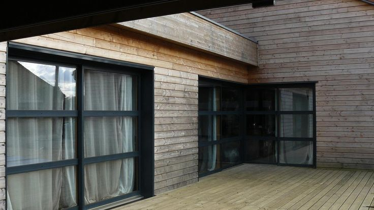 Façade arrière. Extension bois avec terrasse bois courant autour de la maison.